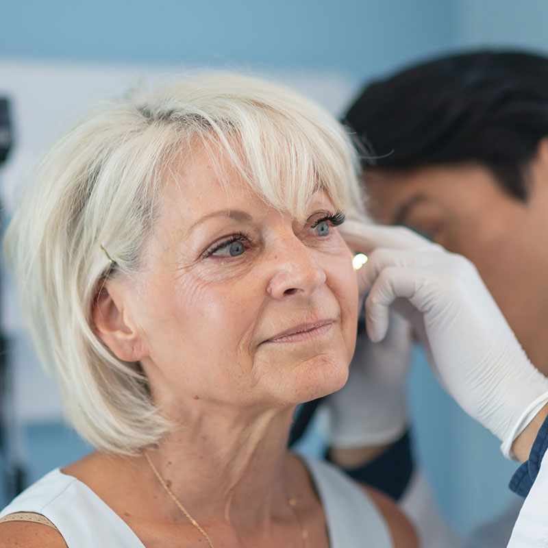 Woman having her ears examined by a doctor to check for causes of hearing loss.